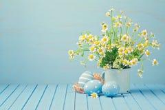 Påskferiegarnering med tusenskönablommor och målade ägg Royaltyfri Bild
