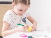Påskfestival: En flicka målar en modell på ett påskägg arkivbilder