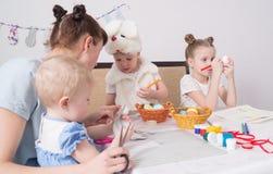 Påskfestival: Familjen på tabellen förbereder sig för ferien Dottern satte en modell på ägget arkivbild