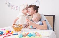 Påskfestival: Familjen på tabellen målar påskägg Sonen i dräkten av påskkaninen kysser hans arkivfoton