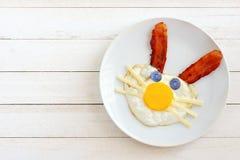 Påskfrukost med kaninframsidan på plattan mot vitt trä Royaltyfria Bilder