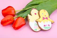 Påskgåvor, söta pepparkakor, blommor på pastellfärgad bakgrund royaltyfria bilder
