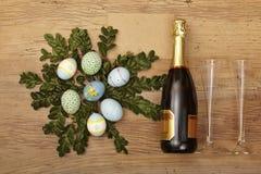 Påskgarnering, champagnerbootle och champagneexponeringsglas på trä fotografering för bildbyråer