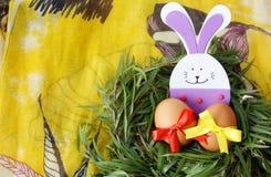 Påskgarnering: gula ägg och hand - den gjorda festliga kaninen för plast- skum i ris för grönt gräs bygga bo på gul bakgrund Royaltyfria Bilder