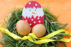 Påskgarnering: gula ägg och hand - gjord kläckt höna i äggskal i ris för grönt gräs bygga bo på orange bakgrund Royaltyfria Bilder