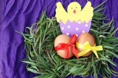 Påskgarnering: gula ägg och hand - gjord kläckt höna i äggskal i ris för grönt gräs bygga bo på purpurfärgad bakgrund Royaltyfri Foto