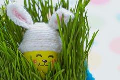Påskgarnering med det gulliga ägget i kaninhatt Arkivbilder