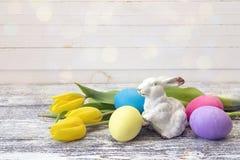 Påskgarnering med kanin, easter ägg och gula tulpan Arkivbild