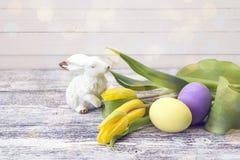Påskgarnering med kanin, easter ägg och gula tulpan Royaltyfri Bild