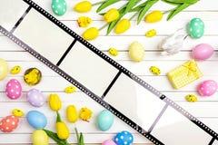 Påskgarneringar med filmbandet på den vita trätabellen arkivfoto