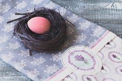 Påskgarneringar med påskägg i ett dekorativt rede på den handgjorda bordduken royaltyfri fotografi