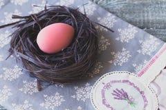 Påskgarneringar med påskägg i ett dekorativt rede på den handgjorda bordduken arkivbilder
