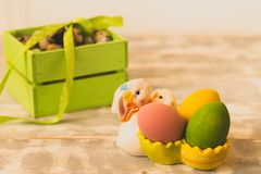 Påskgarneringar med påskägg, keramiska kaniner och band arkivbild