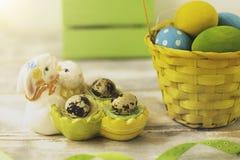Påskgarneringar med påskägg, keramiska kaniner och band arkivfoton