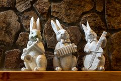 Påskgarneringar på ett stenansvar med vita kaniner arkivfoton