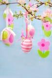 Påskgarneringen med hängande ägg och klädde med filt blommor Arkivfoton