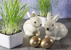 Påskgarneringkaniner och guld- ägg på en grå träbaksida Royaltyfri Foto