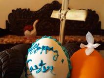 Påskhälsningar på ägget med duvafågelkorset gömma i handflatan Arkivbilder