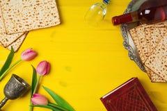 PåskhögtidPesah beröm med matzohen, tulpanblommor och vinflaskan på gul träbakgrund arkivfoto
