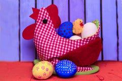 Påskhöna från rött tyg och med filtmellanlägg med ett specialt ställe för att lagra ägg arkivfoton