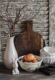 Påskkökstilleben - ägg i en bunke, en vas med torrt ris, keramisk kanin, tappninglerkärl och skärbräda Arkivfoto
