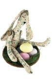 Påskkanin med målade ägg på ett sugrörmagasin Arkivfoton