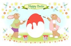 Påskkaninfamilj som målar det stora ägget Arkivfoto