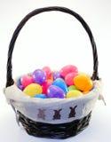 Påskkorg mycket av blandade kulöra easter ägg fotografering för bildbyråer