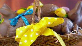 Påskkorgen av chokladägg i korgen, docka avslöjer closeupen