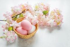 Påskkortet med easter ägg och rosa färger blommar Arkivfoton