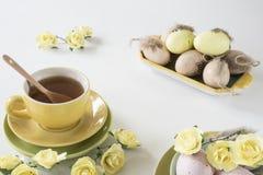 Påskmorgonplats i pastellfärgade färger, med te och rosa och gula ägg royaltyfri bild
