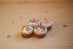 Påskmuffin med kräm- och små konfettier på en trätabell Royaltyfria Foton