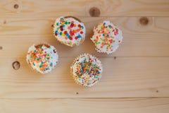Påskmuffin med kräm- och små konfettier på en trätabell Royaltyfri Bild