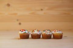 Påskmuffin med kräm- och små konfettier på en trätabell Fotografering för Bildbyråer