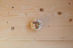 Påskmuffin med kräm- och små konfettier på en trätabell Royaltyfria Bilder