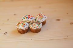 Påskmuffin med kräm- och små konfettier på en trätabell Arkivbild