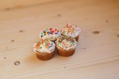 Påskmuffin med kräm- och små konfettier på en trätabell Arkivbilder
