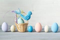 Påskpastell färgade ägg och den lilla korgen med den blåa fågeln på en ljus träbakgrund Royaltyfri Bild