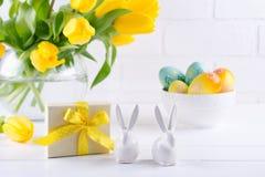 Påsksammansättning med buketten av gula tulpanblommor i exponeringsglasvas och två vita keramiska kaniner på vit royaltyfri fotografi