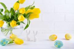 Påsksammansättning med buketten av gula tulpanblommor i exponeringsglasvas och två vita keramiska kaniner på vit arkivbild