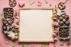 Påsksammansättning med chokladägg, vårblommor, olika garneringar, träkaniner och fåglar på en rosa bakgrund, utrymme Royaltyfri Foto