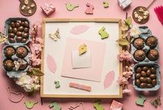 Påsksammansättning med chokladägg, vårblommor, olika garneringar, träkaniner och fåglar på en rosa bakgrund, utrymme Royaltyfri Fotografi