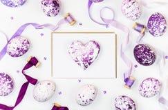 Påsksammansättning med hjärta, målade ägg, paljetter och silkeband på en vit bakgrund Utrymme för en hälsningtext royaltyfri fotografi