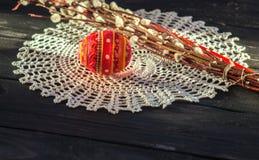 Påskstilleben med det handgjorda souvenirägget och pussypilen Arkivfoto