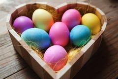 Påsksymbol - hjärta formade bunken mycket av kulöra ägg arkivbilder
