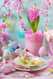 Påsktabellgarnering med ägg och blommor i pastellfärgade färger royaltyfri bild