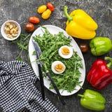Påskvårsallad med nya grönsaker: tomater, arugula, ägg, muttrar och krutonger på en grå grungebakgrund överkant arkivfoton