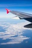 Påskynda flygplanet som flyger ovannämnda moln som ser himlen från wina Arkivfoto