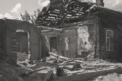 Påverkat som ett resultat av en naturkatastrof, byggnaden av den privata egenskapen Fragment av det förstörda tegelstenträhuset royaltyfri bild