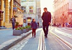 Père à la mode et fils marchant dans la vieille rue de ville Photographie stock libre de droits